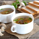 Homemade mushroom soup in a bowl, wheat bread slices on a chopping board, fresh raw mushrooms and green parsley on a wooden table Royalty Free Stock Photos