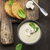 Homemade mushroom soup puree with spinach and a slice of cereal bread on a dark background with a dark ceramic bowl. Top Royalty Free Stock Image