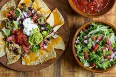 Homemade Nachos with tortilla chips cheese and guacamole Stock Photos