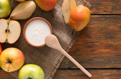 Homemade natural farmer yoghurt for breakfast. In jar with fresh fruits - pears and apples on wooden desk, top view Stock Image
