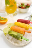 Homemade natural ice pops. Closeup of some different homemade natural ice pops served in a plate with ice, placed on a table with a jar of juice and a bowl with Stock Photography