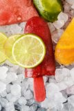 Homemade natural ice pops on crushed ice. High angle view of some different homemade ice pops, made with different natural fruit juices and pieces of fruit, such stock image