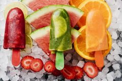 Homemade natural ice pops on crushed ice. High angle view of some different homemade ice pops, made with different natural fruit juices and pieces of fruit, such Stock Photography