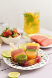 Homemade natural ice pops. Some different homemade natural ice pops in a ceramic plate next to some different pieces of fruit, such as strawberries or watermelon Royalty Free Stock Photos