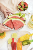Homemade natural ice pops. Young man placing a plate with some slices of watermelon on a table where there is some different homemade natural ice pops in a plate royalty free stock photo