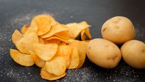 Homemade natural potato chips spicy crisps food. Homemade natural fried chips. spicy crisps snack and fresh organic potatoes dark background. free space concept royalty free stock images
