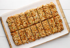 Homemade no bake granola bars with oat flakes, honey, dried apricots and seeds on white baking paper. Royalty Free Stock Photography
