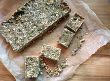 Homemade nut-and-seed energy bars on cutting board. A top-down view of homemade vegan energy bars being cut into pieces on wax paper on a cutting board. The bars Stock Photography