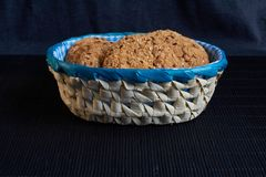 Homemade oat cookies with sunflower seeds in and near blue checkered basket on black background. Homemade oat cookies with sunflower seeds in and near blue Stock Photography