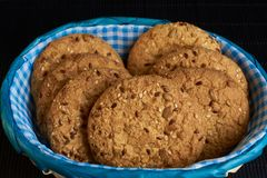 Homemade oat cookies with sunflower seeds in and near blue checkered basket on black background. Homemade oat cookies with sunflower seeds in and near blue Royalty Free Stock Images