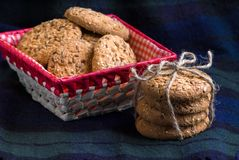 Homemade oat cookies with sunflower seeds in and near red checkered basket on dark blue background. Homemade oat cookies with sunflower seeds in and near red Royalty Free Stock Photos