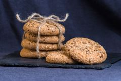 Homemade oat cookies with sunflower seeds on shale board and dark blue textile background. Homemade oat cookies with sunflower seeds on shale board and dark blue Stock Images