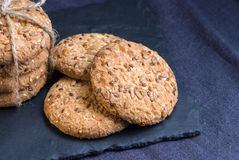 Homemade oat cookies with sunflower seeds on shale board and dark blue textile background. Homemade oat cookies with sunflower seeds on shale board and dark blue Royalty Free Stock Photo