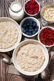 Homemade oatmeal and berries on table, top view. Vertical Royalty Free Stock Images