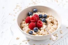 Homemade oatmeal with berries on white wooden table, closeup. Horizontal Stock Image