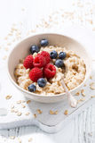 Homemade oatmeal with berries on white wooden table, closeup. Homemade oatmeal with berries on white wooden table, vertical Stock Image