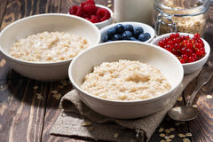 Homemade oatmeal and berries on wooden table. Horizontal Stock Photo