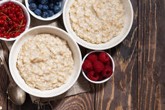 Homemade oatmeal and berries on wooden table, horizontal. Top view Stock Photography