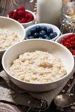 Homemade oatmeal and berries on wooden table, vertical closeup. Homemade oatmeal and berries on wooden table, closeup Stock Photography
