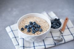 Homemade oatmeal with blueberries and strawberries in bowl on gray concrete background. Healthy breakfast royalty free stock photo
