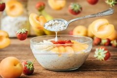 Homemade oatmeal for breakfast with banana, strawberry and apricot. Stock Photos