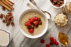 Homemade oatmeal for breakfast. With raspberry, cinnamon and honey overhead shot Stock Photos