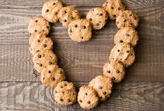Homemade oatmeal cookies with chocolate drops placed in form of heart on the old brown wooden table. Stock Photos