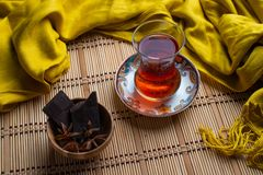 A cup of turkish tea with dark chocolate in bamboo bowl on old wooden background stock photography