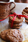 Homemade oatmeal cookies on a metal tray. Homemade oatmeal cookies tied with red ribbon on a metal tray with a clay cup of milk and bread sticks in paper bags stock image