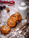 Homemade oatmeal cookies with nuts, raisins, candy cane and bottle of milk on dark wooden background, closeup, selective Royalty Free Stock Photography