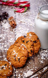 Homemade oatmeal cookies with nuts, raisins, candy cane and bottle of milk on dark wooden background, closeup, selective Royalty Free Stock Photos