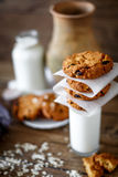 Homemade oatmeal cookies with nuts and raisins and glass of milk on dark wooden background, closeup, selective focus Royalty Free Stock Photography