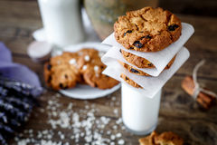 Homemade oatmeal cookies with nuts and raisins and glass of milk on dark wooden background, closeup, selective focus Stock Images