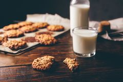 Oatmeal Cookies and Glass of Milk. Homemade Oatmeal Cookies with Raisins and Glass of Milk for Breakfast. Some Cookies on Parchment Paper with Bottle on stock photo