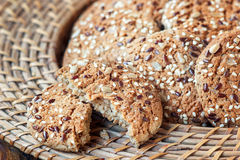 Homemade oatmeal cookies with seeds of cereals in wicker plate for a healthy breakfast, close-up. Horizontal Stock Photography