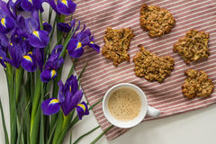 Homemade oatmeal cookies on a striped fabric background on a table with a mug of coffee with spices and flowers of purple iris. Royalty Free Stock Images
