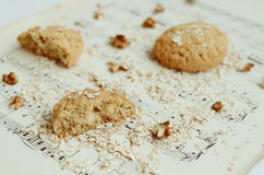 Homemade oatmeal cookies with walnut on vintage music sheet Royalty Free Stock Photos