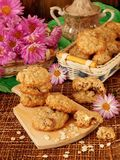 Oatmeal cookies and daisy flowers Stock Images