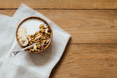 Homemade oatmeal granola with yogurt in wooden bowl. Homemade oatmeal banana granola with yogurt in wooden bowl Stock Photo