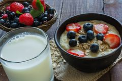 Homemade oatmeal porridge with berries and glass of milk on wooden table Stock Photo
