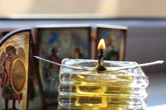 Homemade oil candle and icons. The flame of an old homemade glass oil candle in front of christian orthodox icons Royalty Free Stock Photography