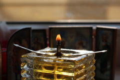 Homemade oil candle and icons. The flame of an old homemade glass oil candle in front of christian orthodox icons in the dark Royalty Free Stock Photography