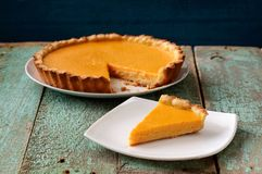 Homemade oldfashioned round pumpkin pie on old table painted blu Royalty Free Stock Photo