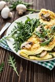 Omelette with mushrooms and arugula on a wooden background stock photo