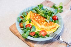 Homemade omelette with salad on plate. Healthy food concept stock photo
