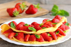 Homemade omelette stuffed with fresh strawberries on a white plate. Delicious and healthy egg omelette recipe idea Royalty Free Stock Photo