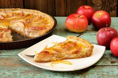 Homemade open apple pie and whole red apples on vintage table Royalty Free Stock Images