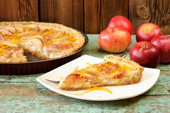 Homemade open apple pie and whole red apples on vintage table Stock Image