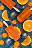 Homemade orange and carrot natural juice popsicles with turmeric, honey and ginger. Stock Photos
