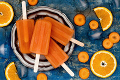 Homemade orange and carrot natural juice popsicles with turmeric, honey and ginger. Royalty Free Stock Photos